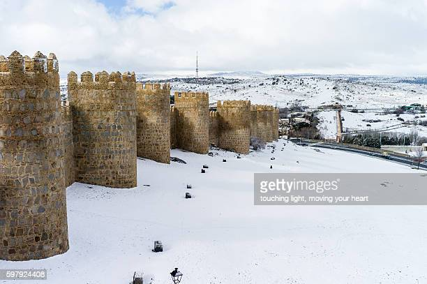 town wall standing in white snow, avila, spain - avila stock photos and pictures
