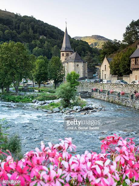Town with its church and streets, in a mountain village in the Pyrenees, next to a large river.