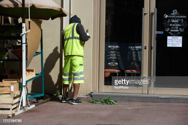 Townhall employee cuts vegetation growing in the cracks. Since the beginning of the lockdown due to the Covid-19 outbreak in France on March 16th,...