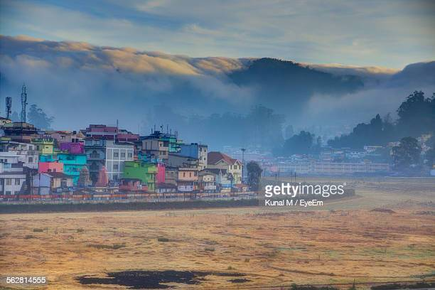 Townscape Against Clouds Covered Mountain