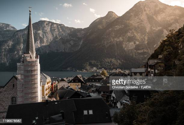 townscape and mountains by lake against sky - soldatke stock-fotos und bilder