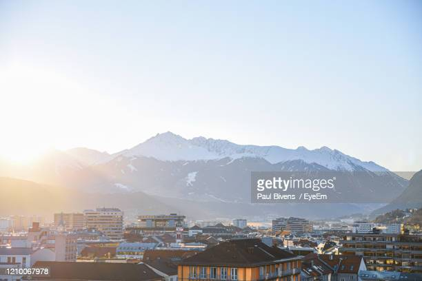 townscape by mountains against clear sky during winter - innsbruck stock pictures, royalty-free photos & images