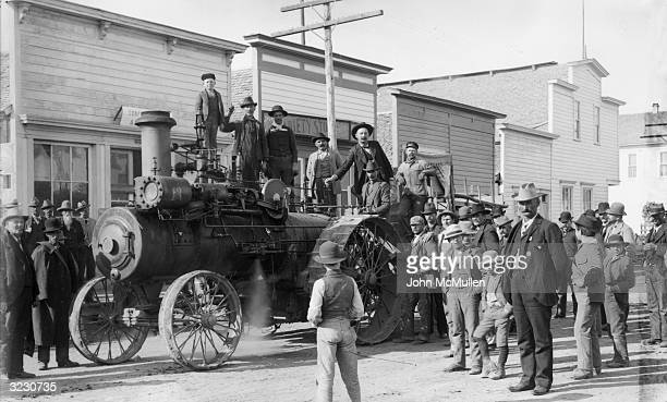 Townspeople gather in the road as the Russell steam engine arrives on the main street in Burns Oregon Six men and a young boy stand on the engine...