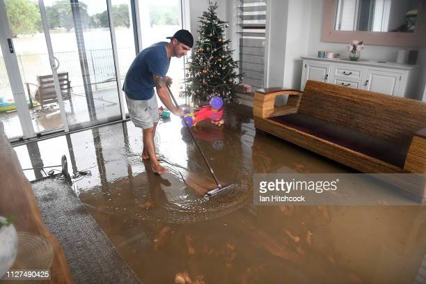 Townsville resident David Mitchell sweeps out his muddy loungeroom after flood waters receded in the suburb of Rosslea on February 05 2019 in...