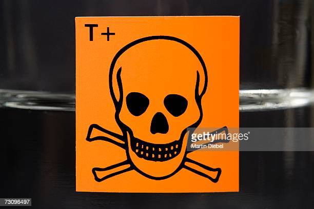 Toxic substance label with skull and crossbones on glass flask containing liquid