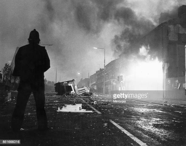 Toxteth Riot 5th July 1981 A police officer in riot gear stands amongst the broken glass and burning shops in Park Road The riots was sparked...