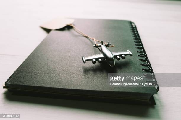 Toy Airplane And Spiral Notebook On Desk