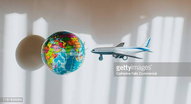 toy airplane flying towards a globe - flying stock pictures, royalty-free photos & images