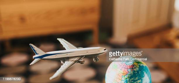 toy airplane flying towards a globe - globe stock pictures, royalty-free photos & images