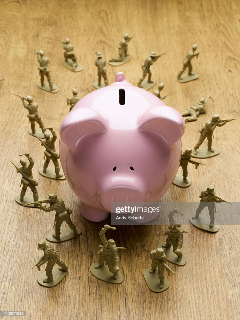 Toy army men surrounding piggy bank : Stock Photo