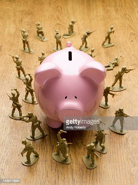 toy army men surrounding piggy bank - army soldier toy stock pictures, royalty-free photos & images
