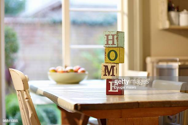 Toy bricks and bowl of fruit on kitchen table.