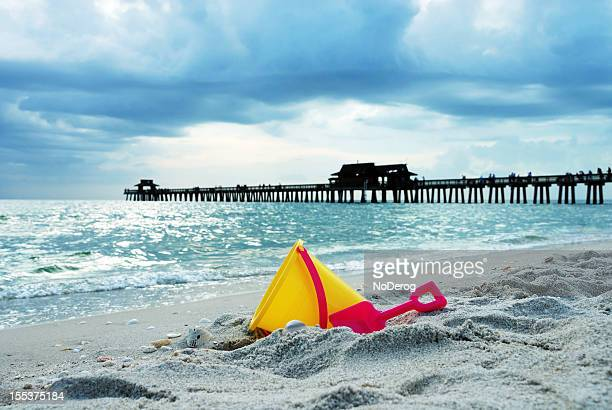 toy bucket on beach with pier in background - naples florida stock pictures, royalty-free photos & images