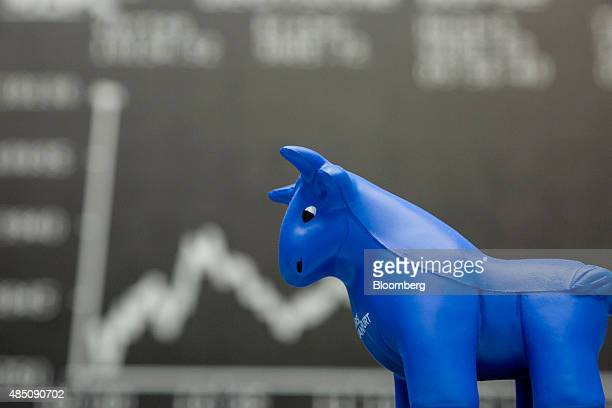 A toy bull figurine sits on a financial trader's desk as the DAX Index curve is displayed on an electronic board behind at the Frankfurt Stock...