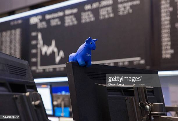 A toy bull figurine sits on a financial trader's desk as the DAX Index curve is displayed beyond inside the Frankfurt Stock Exchange in Frankfurt...