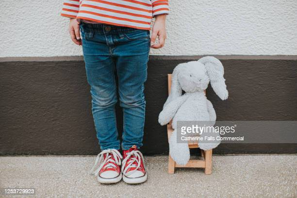 toy bunny sitting on a wooden chair, against an external wall, as child stands beside it. - rabbit stock pictures, royalty-free photos & images