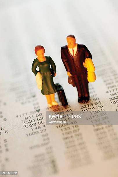 Toy businessman and businesswoman standing on top of paper with financial figures