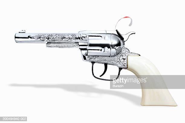 Toy cap gun against white background, close-up