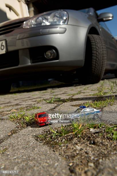 A toy car crash with a toy police car, real car in background