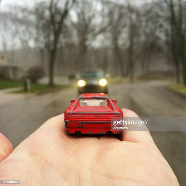 Toy car in man's hand facing a real car in the street