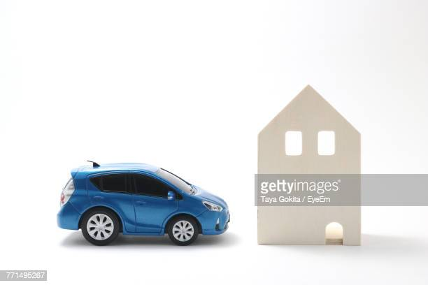 Toy Car With Model House Against White Background