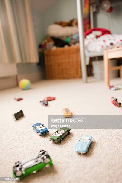 Toy cars scattered across a child's bedroom
