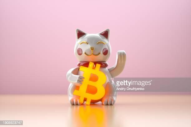 toy cat holding glowing bitcoin sign - zwaaien gebaren stockfoto's en -beelden