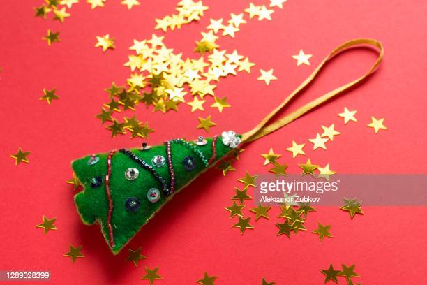 toy christmas tree handmade from felt, confetti in the form of gold stars on a red christmas background. - ビーズ ストックフォトと画像