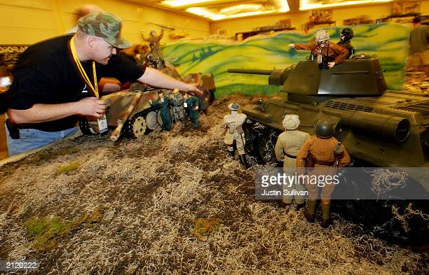 Toy dealer Greg Brown adjusts an action figure in his diorama at the 2003 Hasbro International GI Joe Collectors' Convention June 27 2003 in...
