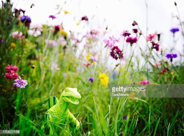 toy dinosaur in garden with flowers