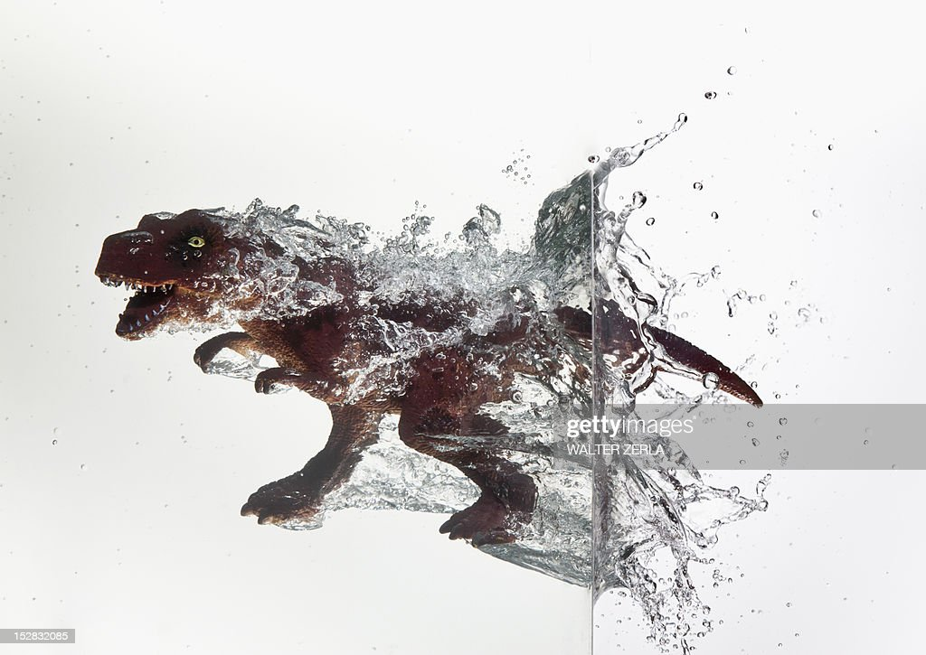 Toy dinosaur plunging into water : Stock Photo
