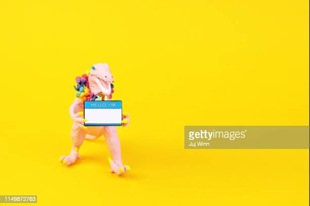 "toy dinosaur with ""hello i'm"" name tag - dinosaur stock pictures, royalty-free photos & images"
