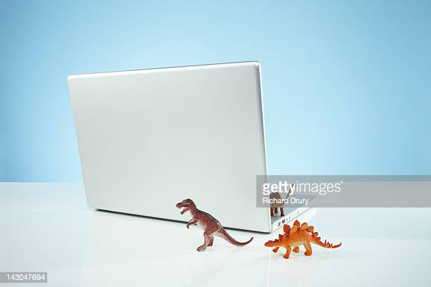 Toy dinosaurs emerging from Laptop