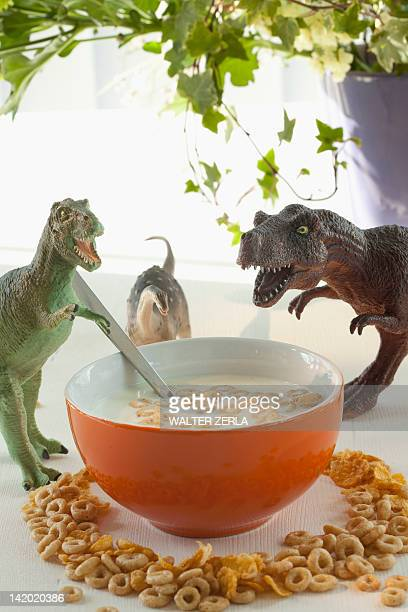 toy dinosaurs with bowl of cereal - furioso foto e immagini stock