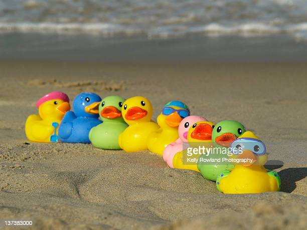 Toy ducks in row on sand