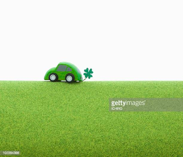 Toy eco car on the green ground.