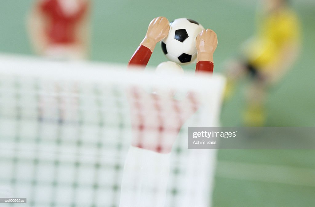 Toy figurine playing football, Tipp Kick, blurred image : Stock Photo