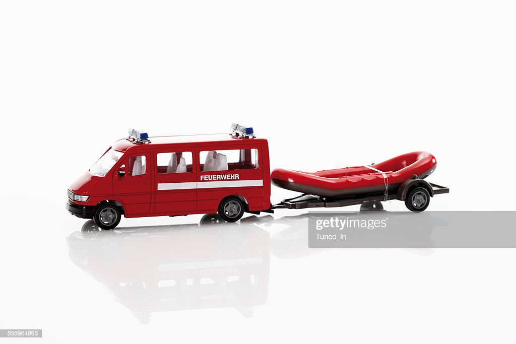 Toy fire truck with rubber raft on white background : Stock Photo