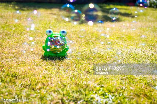 Toy frog on lawn blowing bubbles