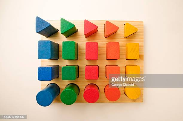 toy geometric blocks in pegs, overhead view - triangle percussion instrument stock photos and pictures