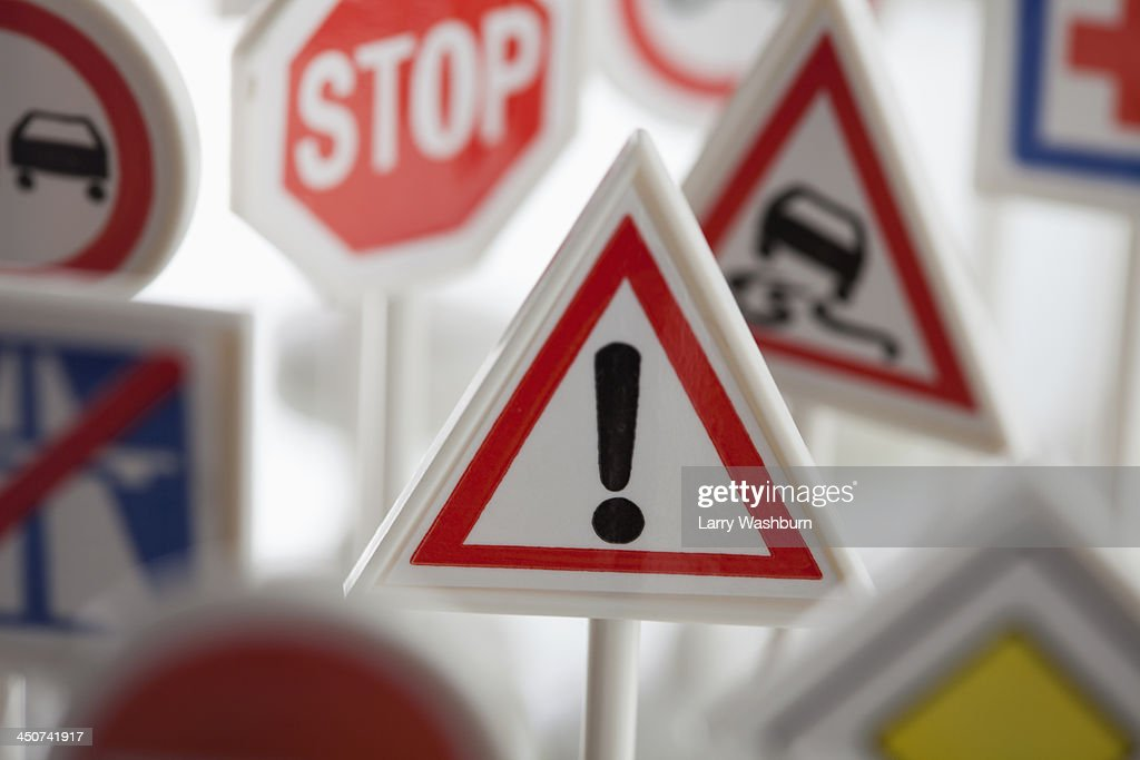 A toy hazard sign surrounded by other various road warning signs : Stock Photo