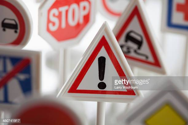 a toy hazard sign surrounded by other various road warning signs - warning sign stock pictures, royalty-free photos & images