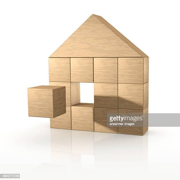 Toy house made of wooden blocks on white