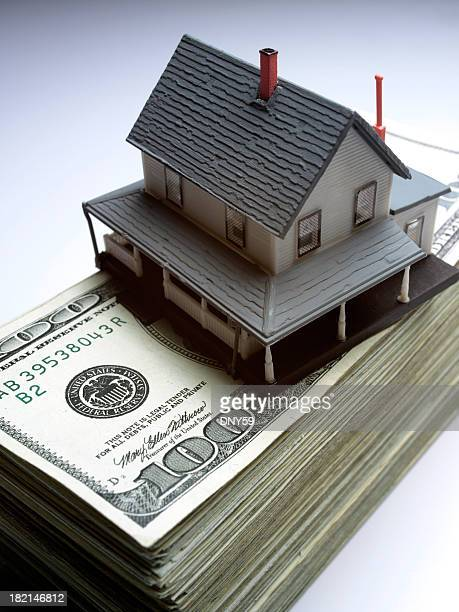 Toy house on top of stack of money