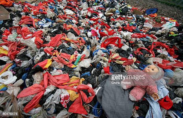 A toy is abandoned on plastic bags at an open dump on April 2 2008 in Chongqing Municipality China The Chinese government has announced a nationwide...