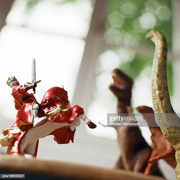 Toy knight fighting against toy dinosaurs.