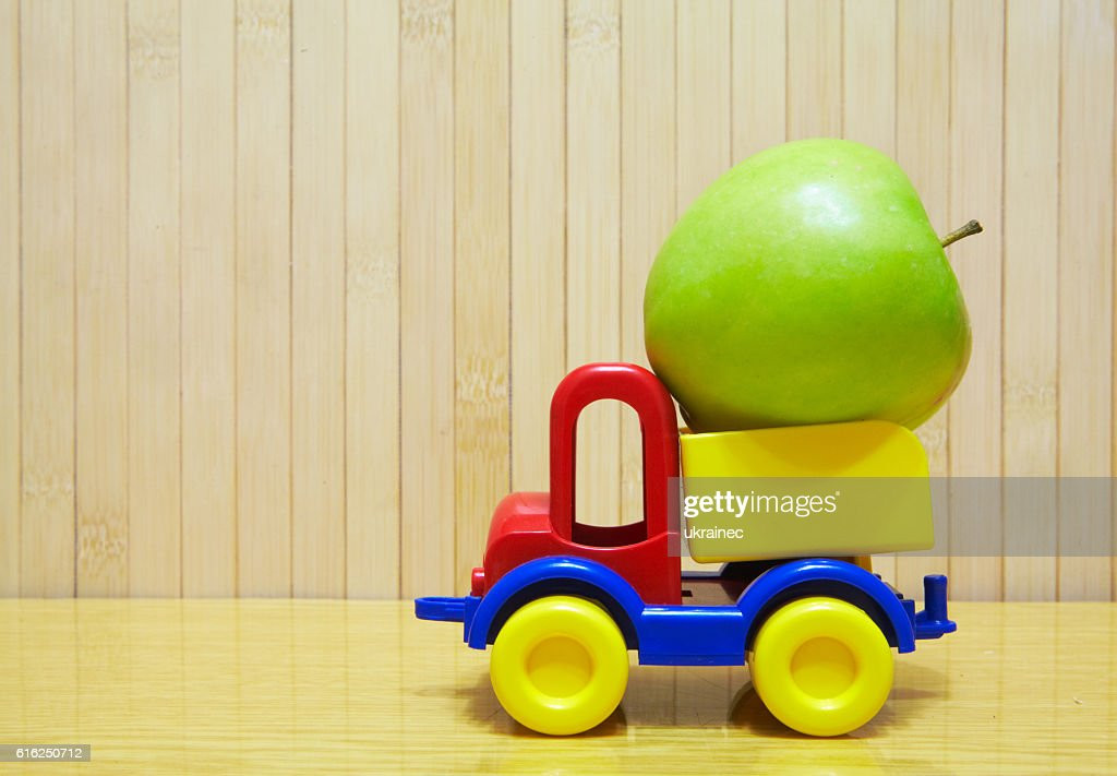 Toy plastic car with green apple : Stock Photo