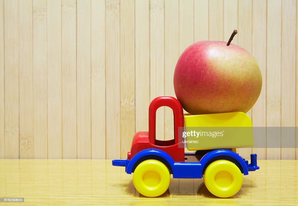 Toy plastic car with red apple : Foto de stock