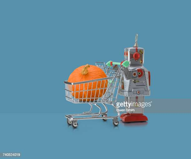 Toy robot pushing miniature shopping trolley with pumpkin against blue background