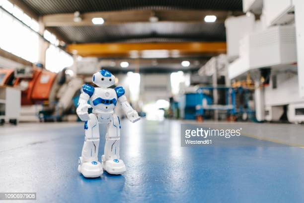 toy robot standing on floor of factory workshop - innovation stock-fotos und bilder
